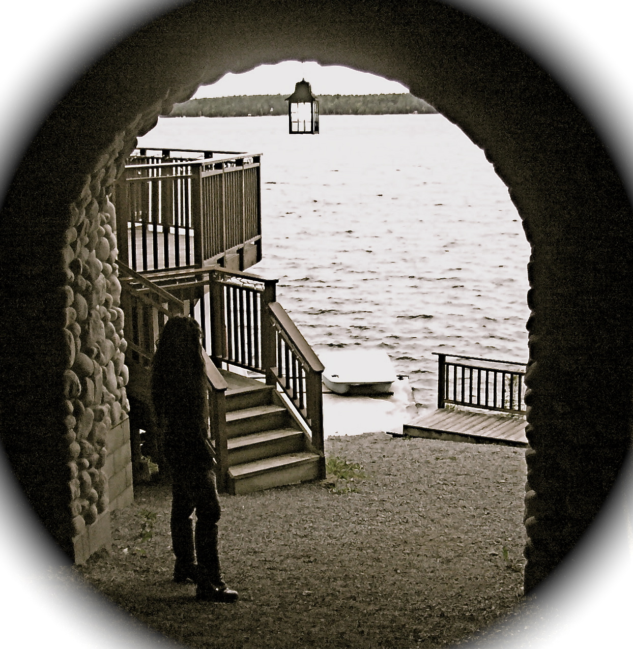 woman stands looking out at the water from a stone archway