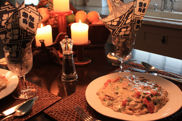 diner setting with pasta and mushroom sauce, wine glasses, and candles