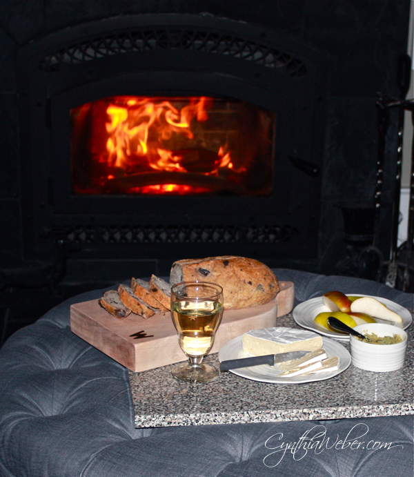 beautiful meal of cheese and bread displayed infront of the fire