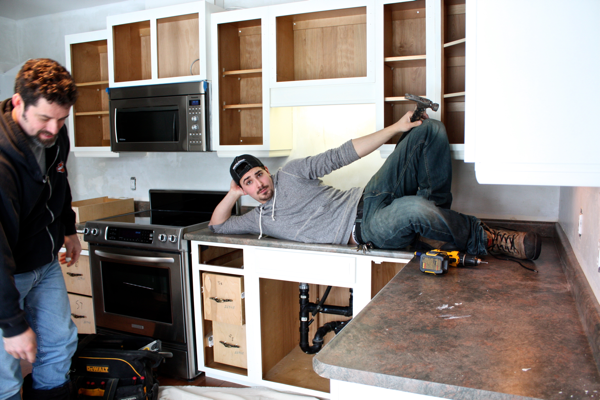 Spencer posing for one more pic before removing old countertops… cynthiaweber.com