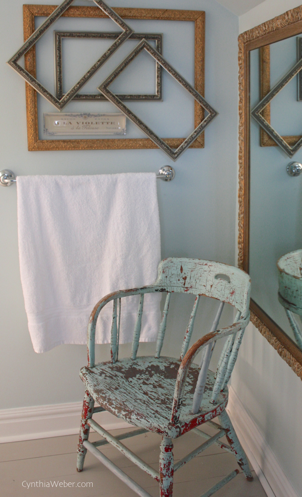 Layered frames in mixed metal finishes and an unexpected french inspired vanity tray make a fun vignette in this vintage bathroom reno CynthiaWeber.com